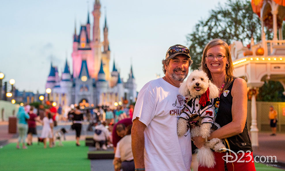A pirate poodle poses with his owners on the green carpet.