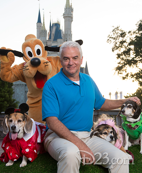 Actor John O'Hurley poses with Pluto and three Disney-dressed dogs.