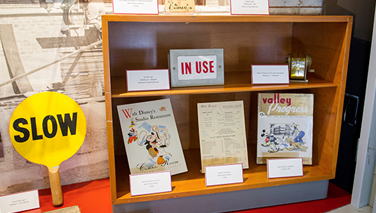 Commissary menus, an employee handbook, equipment, and signage all help tell the story of day-to-day life at the Disney Studio.