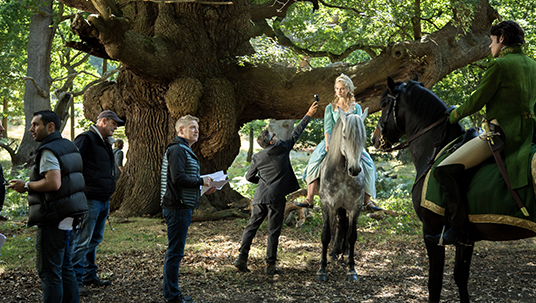 photo from the forest set of Cinderella featuring director Kenneth Branagh, and stars Lily James & Richard Madden