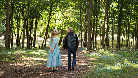 production photo of actress Lilly James and director Kenneth Branagh on the forest set of Cinderella
