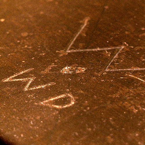 close up of initials W D carved into wooden surface of school desk