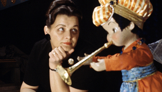 Disney Legend Alice Davis looking at a puppet