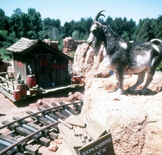 photo of Audio-Animatronic mountain goat atop a cliff overlooking tracks and utility shed of Big Thunder Railroad attraction at Disneyland