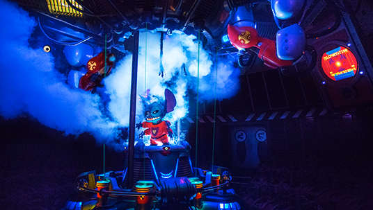 photo of gremlin-like creature surrounded by plumes of steam and brightly colored machinery