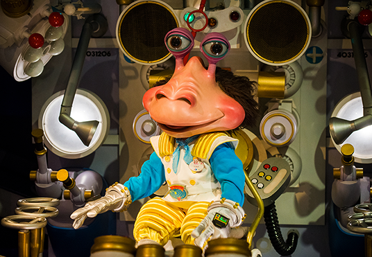 photo of humanoid creature with a head like a fat nose that has a pair of bug eyes on stems wearing bright uniform and seated in a command center of a machine