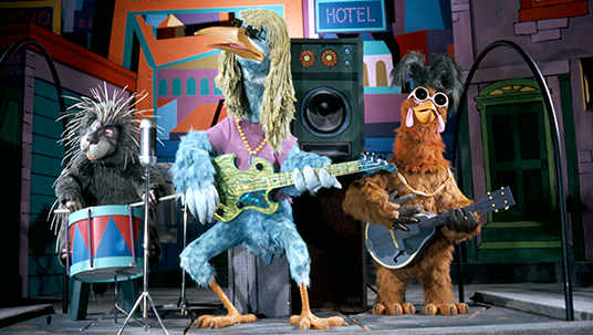 photo of three-member rock band comprised of a porcupine, a tall blue bird, and a hawk wearing sunglasses