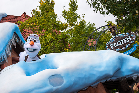 photo of talking Audio-Animatronic Olaf the Snowman popping up out of a snowdrift at the Frozen meeting spot at Disneyland