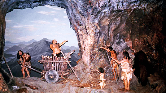 photo of caveman exhibit showing family using primitive tools