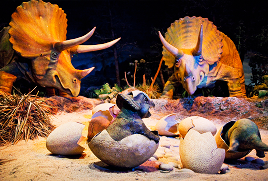 photo of dinosaur models representing full-grown ones and hatchlings emerging from shells