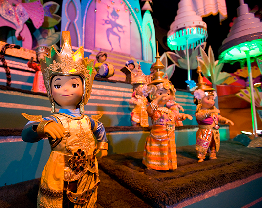 photo of colorfully dressed dolls standing on elaborately decorated stage