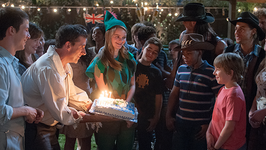 still from movie Alexander and the Terrible, Horrible, No Good, Very Bad Day the showing young boy's father bringing him a birthday cake with lit candles as large group of older kids looks on