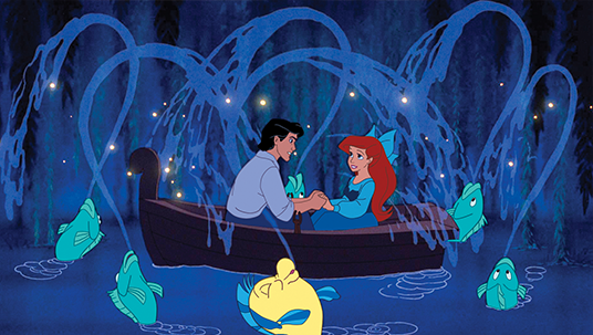 scene from animated feature The Little Mermaid showing fish spouting water over the two lovers holding hands sitting in a row boat