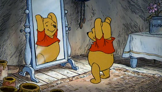 still from animated Winnie the Pooh showing Pooh looking at himself in a full-length mirror while stretching his hands into the air
