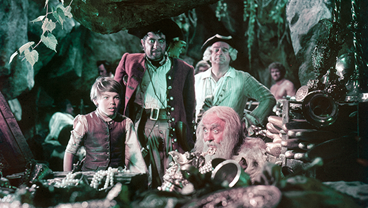 scene from movie Treasure Island showing a young boy staring at loot clutched by pirates in a cave