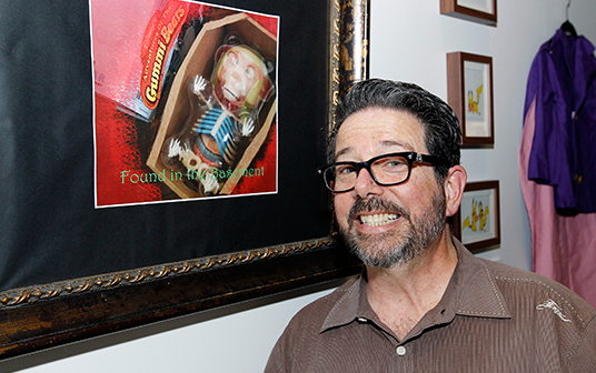 photo of Rob LaDuca standing next to his framed illustration of Gruffy the zombie Gummy Bear
