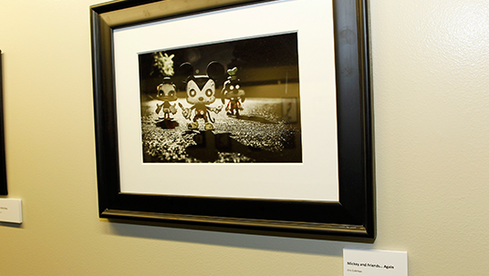 framed photo by Eric Coleman of three small figurines representing zombie versions of Donald Duck, Mickey Mouse, and Goofy creeping toward camera
