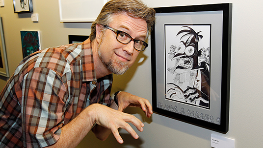 photo of Dan Povenmire with his framed illustration of a zombie character