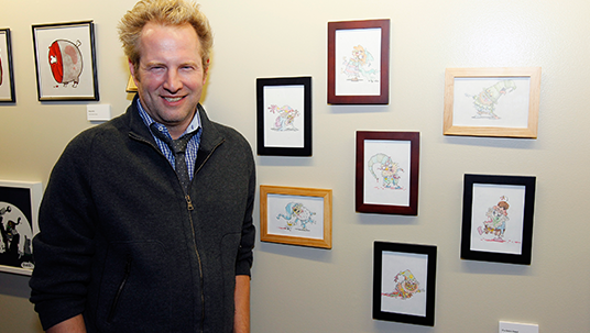 photo of The 7D co-executive producer Tom Warburton with his seven illustrations of the Seven Dwarfs