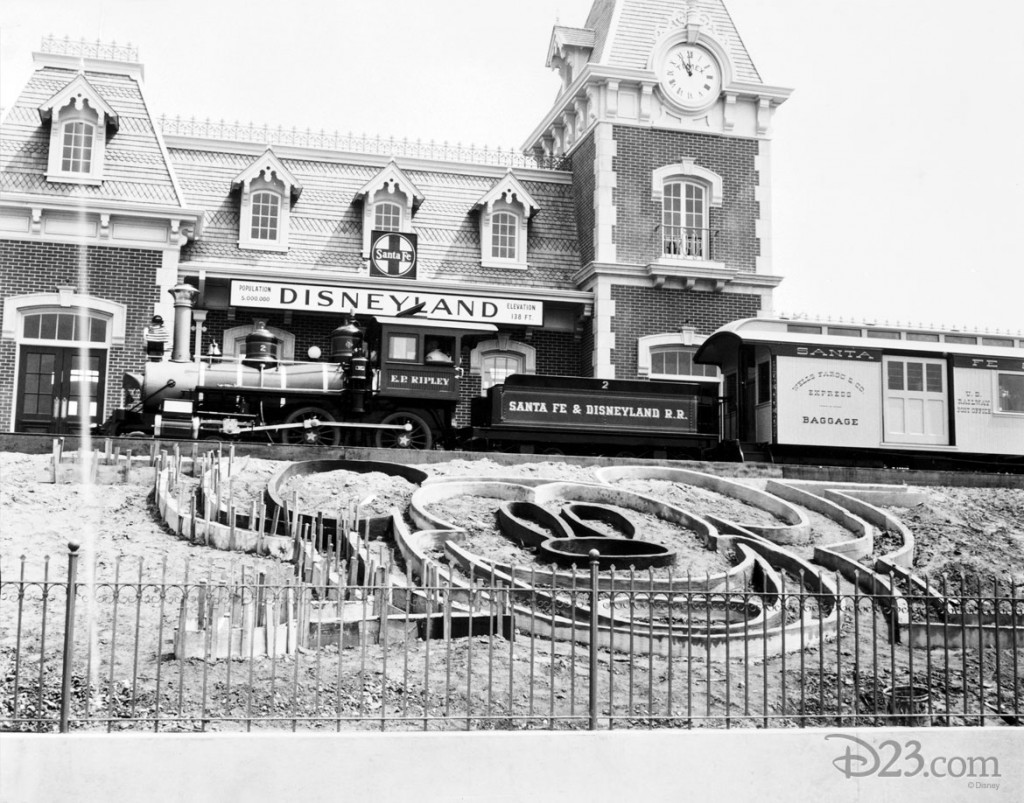 black and white photo of Disneyland prior to opening showing train station and E.P. Ripley engine mounted on Santa Fe and Disneyland Railroad cars with beginning Mickey Mouse floral bed partially completed in foreground