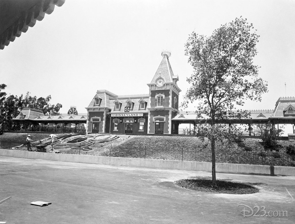 black and white photo of Disneyland prior to opening showing workers laying out forms on sloping ground for Mickey Mouse floral bed partially completed in foreground