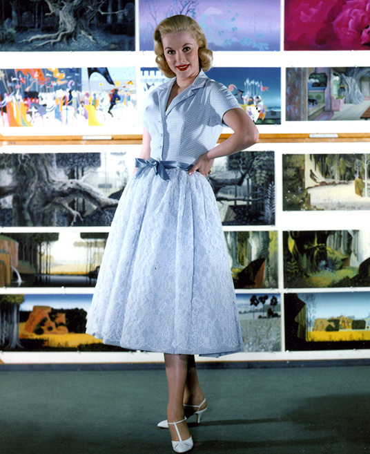 photo of Mary Costa posing in front of artists' paintings