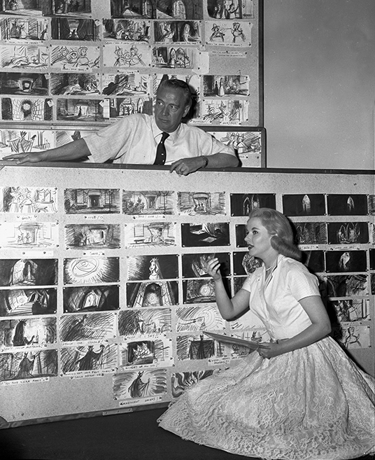 black and white photo of Mary Costa with large storyboards of artists' sketches for Sleeping Beauty