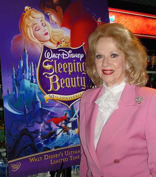 photo of Mary Costa in later life posing with Sleeping Beauty poster