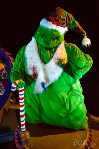 photo of character in bright green costume wearing white fur trimmed cap and coat and holding a large red-white-and-blue striped candy cane