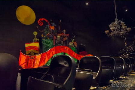 photo of portion of Haunted Mansion ride showing string of empty ride cars beside bright red Scary Christmas banner