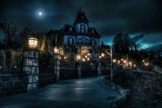 photo of Disneyland's Haunted Mansion at night looking creepy
