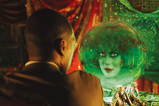 photo of Eddie Murphy looking at woman's face apparition in a crystal ball in photo of Disneyland's Haunted Mansion attaction