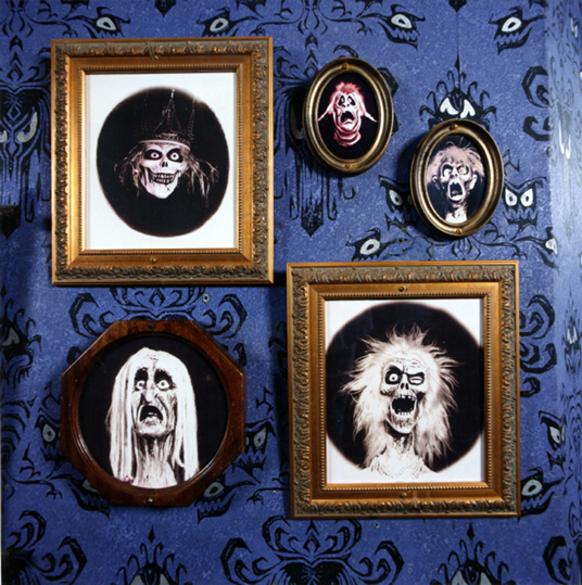 "photo of several framed portraits of ghouls on wall featuring eyes designed by ""Museum of the Weird"" creator Rolly Crump and Claude Coats"
