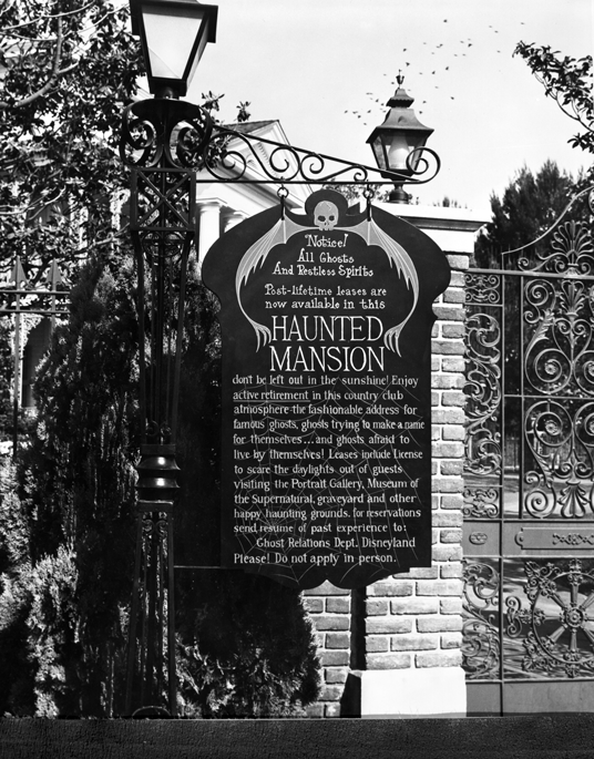 photo of sign posted at front gate of The Haunted Mansion begins with Notice! All Ghosts and Restless Spirits