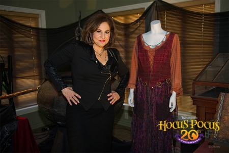 Actress Kathy Najimy (Mary Sanderson) poses next to her costume in the Walt Disney Archives display.