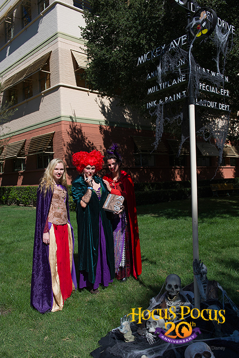 D23 Members, dressed as the Sanderson sisters from <em>Hocus Pocus</em>, pose in front of the famous intersection of Mickey Ave. and Dopey Drive.