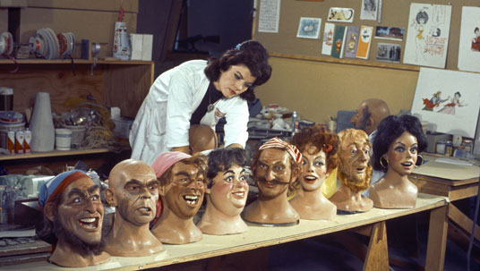 photo of Imagineer Leota Toombs, Madame Leota's face and namesake from the Haunted Mansion attraction, with busts from an assortment of characters from Disneyland attractions including Pirates of the Caribbean