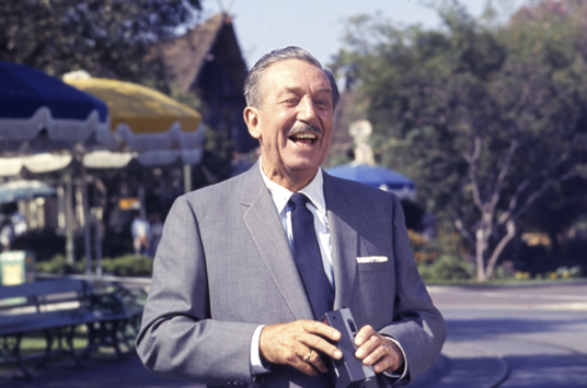 Walt Disney stands near the Central Plaza, ready to capture another gorgeous Disneyland day on film.