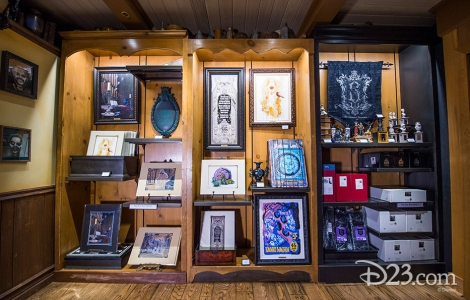 photo of merchandise displayed including framed illustrations based on Haunted Mansion