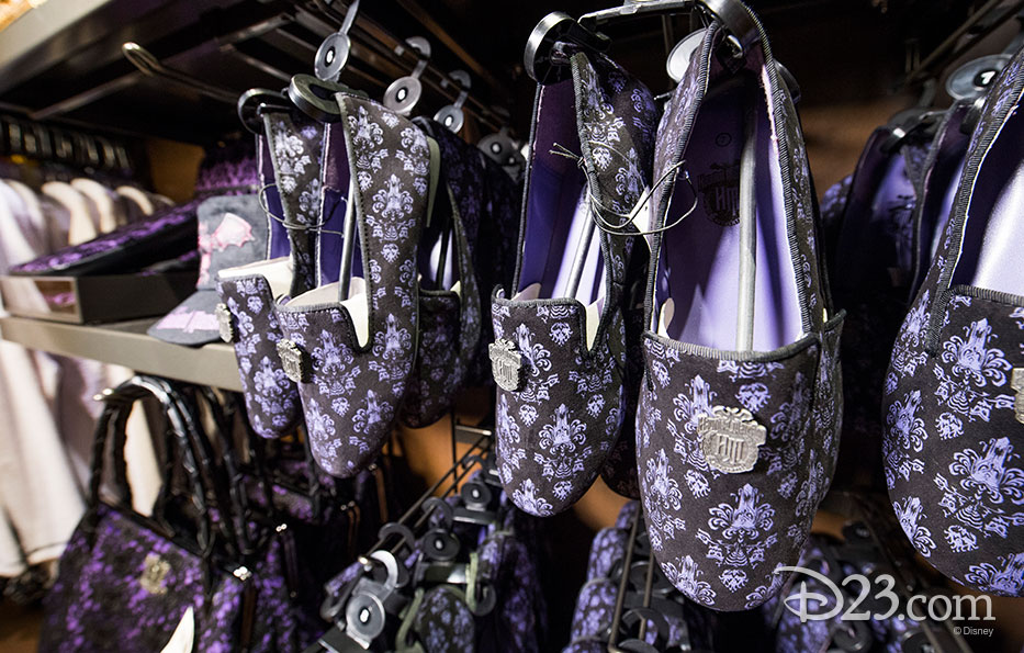 photo of merchandise displayed including purple and black Haunted Mansion slippers and purses
