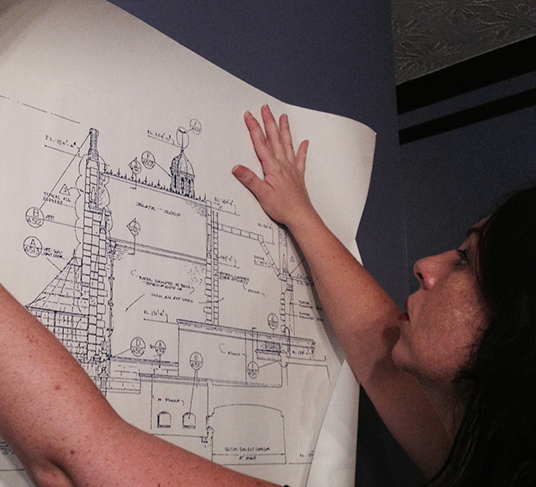 photo of Holly Frey holding up blueprint of Haunted Mansion