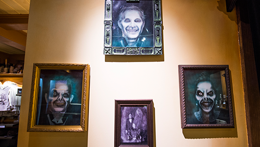 photo of wall on which are hung four framed illustrations of ghouls and creepy looking people