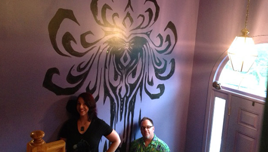 photo of Holly Frey and Brian Frey beside purple and black stairway wall at foyer