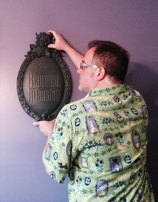 photo of Brian Frey hanging a egg-shaped placard replica of The Haunted Mansion front sign