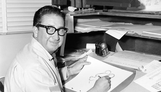 black and white photo of Francis Xavier Atencio, also known as X Atencio, is a former animator and Imagineer for The Walt Disney Company, seated sketching Winnie the Pooh