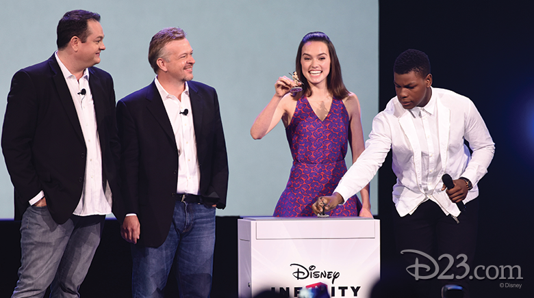 photo of cast of Star Wars The Force Awakens presenting play set action figures on stage, including actors John Boyega and Daisy Ridley plus John Blackburn, senior vice president and general manager of Disney Infinity, and John Vignocchi, vice president of production