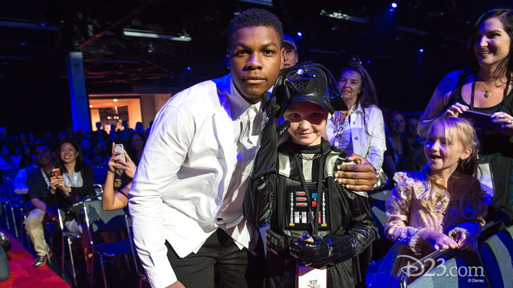 photo of actor John Boyega posing with small boy dressed in Darth Vader outfit