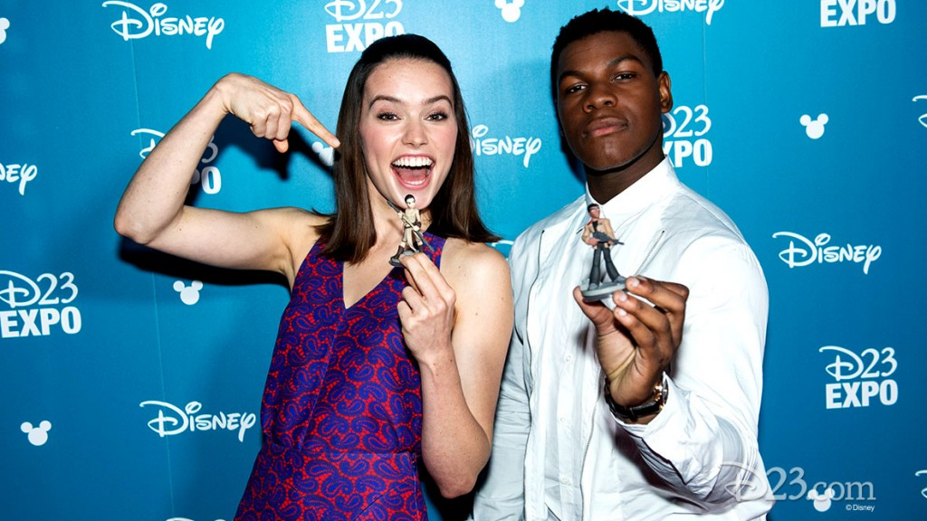 photo of Daisy Ridley and John Boyega posing with action figures of their Star Wars characters