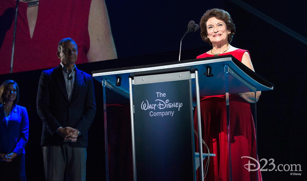 photo of Disneyland Ambassador Julie Reihm Casaletto at podium receiving Disney Legends Award as Robert Iger looks on