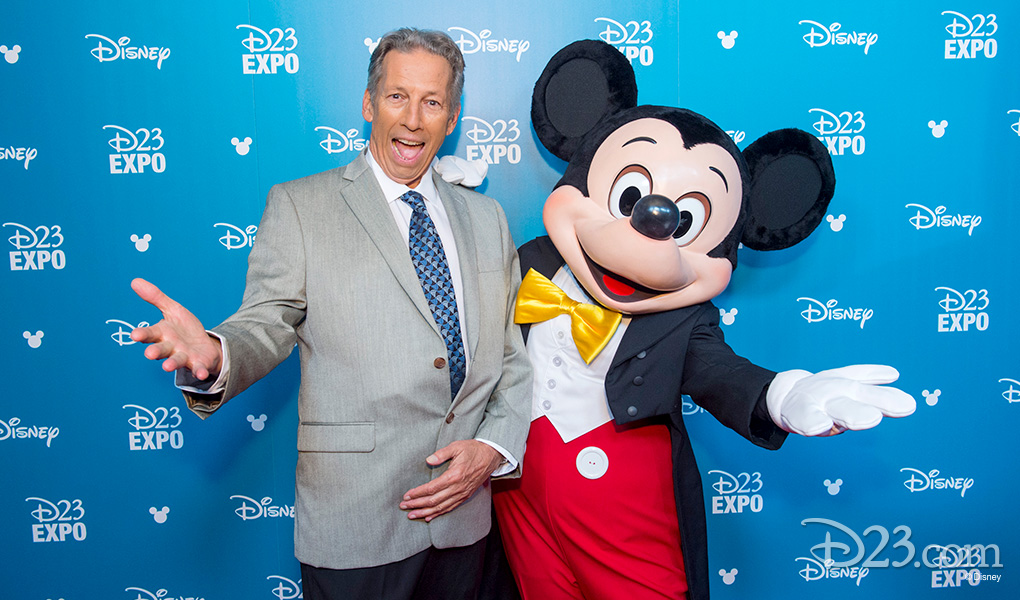 photo of Carson Von Osten with Mickey Mouse after receiving Disney Legends Award